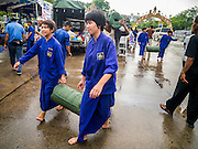 23 NOVEMBER 2012 - BANGKOK, THAILAND:  Members of the Pitak Siam anti-government carry supplies into their base in Bangkok Friday. Thai authorities have imposed the Internal Security Act (ISA), that enables police to call on the army if needed to keep order, and placed thousands of riot police in the streets around Government House in anticipation of a large anti-government protest Saturday. The group sponsoring the protest, Pitak Siam, said up to 500,000 people could turn out to protest against the government. They are protesting against corruption in the current government and the government's unwillingness to arrest or pursue fugitive former Prime Minister Thaksin Shinawatra, deposed in 2006 coup and later convicted on corruption charges. The current Thai Prime Minister is Yingluck Shinawatra, Thaksin's sister.      PHOTO BY JACK KURTZ