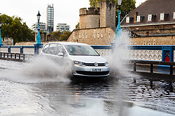 © Licensed to London News Pictures. 06/10/2019. London, UK. A car drives through flooding and excess surface water on Tower Bridge this morning following heavy rain and wet weather in the capital last night. Weather forecasts predict that most of the UK will be experience heavy rain and storms during the next few days. Photo credit: Vickie Flores/LNP