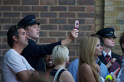LONDON, ENGLAND - Wednesday, June 23, 2010: A security helper takes a photograph on a cameraphone of the record-breaking marathon Gentlemen's Singles 1st Round match, which ended due to bad light at 59-59 in the fifth set, on day three of the Wimbledon Lawn Tennis Championships at the All England Lawn Tennis and Croquet Club. (Pic by David Rawcliffe/Propaganda)