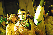 Members of the public are standing on the side of the street during the night parade marking the end of the first day of the Carnival of Ivrea, pop. 30.000. During the days of the Carnival, the town becomes crammed with tourists coming to witness the event which finds its roots at the end of the XII Century, when the people led an insurrection against the local tyrant, Count Ranieri of Biandrate, who was exercising the 'jus primae noctis' rule (having the first night) on the local young brides. The battle to overthrow him is represented with a 3-day-fight between factions in which more then 400 tonnes of oranges are thrown. During the celebrations, food stalls, bands playing music, and parades are also present, giving it a typical Medieval atmosphere.