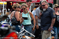 Heather Callen with motorcycle event MC Pat JansenPerewitz Paint Show at the Iron Horse Saloon during the Sturgis Black Hills Motorcycle Rally. SD, USA. Wednesday, August 7, 2019. Photography ©2019 Michael Lichter.
