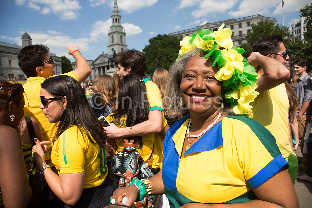 London, UK. Thursday 12th June 2014. Brazilians gather for the Brazil Day celebrations in Trafalgar Sq. A gathering to celebrate the beginning of the Brazil 2014 FIFA World Cup. Revellers sing and dance and play football games and all in the yellow green and blue of the Brazilian flag.