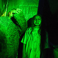 Verna Tsosie and her grandfather Vernon Tsosie Sr. take their places in the Tsosie family haunted house in Deer Springs Wednesday.
