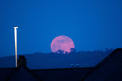 ©Licensed to London News Pictures. 19/04/2019 Aberystwyth UK, A spectacular full moon, know as the 'Pink Moon' lives up to its name as it rises over the hillside near Aberystwyth on Good Friday evening after a day of scorchingly hot sunshine. Photo credit Keith Morris/LNP