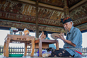 A man painting a fan in the Taman Kertha Gosa temple in Semapura aka Klungkung, is an 18th Century Hindu Balinese temple with an intricately painted ceiling showing scenes from the Bhima Swarga, on 13th June 2018 in Bali, Indonesia. Kertha Gosa means the place where the king meets with his ministries to discuss questions of justice.
