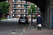 Man walks under the old railway arches near to council flats in Tower Hamlets, East London. Many people are at risk of losing their homes in London with the introduction of new benefit rules, which may push many people renting or who own council apartments out of the city. Tower Hamlets is a poor and over populated borough with many people living in small homes in high rise apartment blocks.