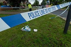 © Licensed to London News Pictures. 08/08/2021. LONDON, UK.  A police officer next to a discarded medical kit bag on the ground cordon outside West Harrow Park in north west London.  According to reports, emergency services were called shortly after 8.30pm on 7 August where they treated a 17-year-old boy, who had knife wounds, at the park before he was taken to hospital.  Later, a 15 year old boy arrived at a hospital's A&E himself with stab wound and he is currently being treated.  Photo credit: Stephen Chung/LNP