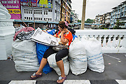 06 JUNE 2013 - BANGKOK, THAILAND:  A clothing vendor in Bangkok's Bobae Market reads the daily newspaper before going to her shop. Bobae Market is a 30 year old market famous for fashion wholesale and is now very popular with exporters from around the world. Bobae Tower is next to the market and  advertises itself as having 1,300 stalls under one roof and claims to be the largest garment wholesale center in Thailand.       PHOTO BY JACK KURTZ