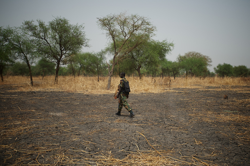 April 24, 2012 - Lalop, South Sudan: A SPLA soldier walks by a field, recently bombed by Sudan troops, in the outskirts of a newly established military base in the village o Lalop, 50 kilometers north of Bentiu...South Sudan and their northern neighbors, Sudan, have in the past two weeks been involved in heavily clashes over border disputes. Bentiu and neighboring villages have been under constant bombardment by the troops os Karthoum , who established their positions around 10 kilometers into South Sudan's territory. The international community is concerned about the possibility of a full on war between the two countries. (Paulo Nunes dos Santos/Polaris)