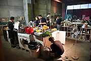 """Cooking in the restaurant, whilst repair, building and maintenance work to utilities goes on <br /><br />The Freegan Pony is an alternative restaurant housed in a squat. It was founded in 2015 by Aladdin Charni with three other collaborators. The restaurant specialises in cheap vegetarian cuisine, serving meals which guests reserve a place through a Facebook group, paying €2 a meal. The restaurant meals contain unsold and donated food, collected from wholesellers at the Paris Rungis vegetable market. The Freegan Pony is located at the Porte de la Vilette on the outskirts of Paris, at the entrance to the peripherique outer circle motorway.<br /><br />Freegans are people who employ alternative strategies for living based on limited participation in the conventional economy and minimal consumption of resources. Freeganism is the practice of reclaiming and eating food that has been discarded. People who attempt to live an ethical lifestyle by reusing trash and rubbish thrown away by others.<br /><br />Freeganism is an ill-defined activity and is a subset of the larger anti-capitalist and environmental protest movements. It embraces alternative, anti-consumerist lifestyles. Freegan practices also include co-operative living, squatting and """"freecyling"""", or matching things that people want to get rid of with things other people need"""