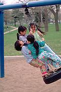 Kids age 11 and 7 swinging at Powderhorn Park May Day Festival.  Minneapolis  Minnesota USA