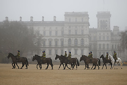 © Licensed to London News Pictures. 03/03/2021. London, UK. Members of The Household Cavalry Mounted Regiment cross a foggy Horse Guards Parade in central London. Later Chancellor Rishi Sunak will deliver his budget to Parliament. Photo credit: Peter Macdiarmid/LNP