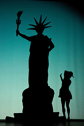 "© Licensed to London News Pictures. 12 March 2014. London, England. Pictured: Statue of Liberty. Pilobolus dance troupe presents ""Shadowland"", a show part dance, part circus, part concert utilising multiple moving screens. ""Shadowland"" is performed for the first time in the UK. Created in collaboration with Steven Banks and featuring a score by David Poe, the show will run from 11 March to 30 March 2014 at the Peacock Theatre, London. Photo credit: Bettina Strenske/LNP"