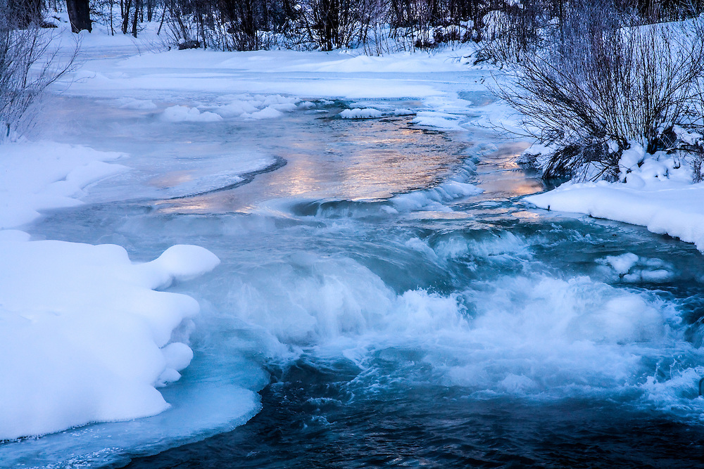 Wood River north of Ketchum, Sun Valley, Idaho in sub-zero temps is partially frozen with a little sunrise color reflection to contrast to cold blue of snow and ice. Licensing and Open Edition Prints.