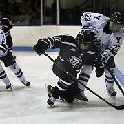Daniel Ciampini, Union College, (centre), challenges Tommy Fallen, Yale, (right), during the Yale Vs Union College, Men's College Ice Hockey game at Ingalls Rink, New Haven, Connecticut, USA. 28th February 2014. Photo Tim Clayton