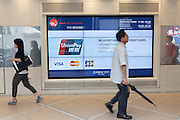 People pass by an advertising screen detailing tax free facilities and credit card acceptance for tourists visiting Japan. Shinjuku, Tokyo, Japan. Wednesday June 29th 2016