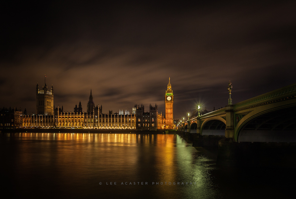 Westminster bridge and the houses of parliament reflected in the River Thames at night