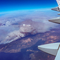An airliner flies over the Mendocino complex of wildfiles burning near Clear lake, California in the summer of 2018.