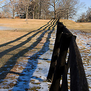 A wooden fence casts long shadows on a winter day in rural Loudoun County, VA