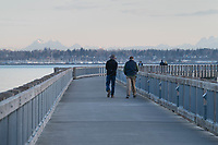 Two adult males walking on Boulevard Park Boardwalk, Taylor Dock on Bellingham Bay, Bellingham Washington