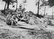 World War I 1914-1918: Wounded German soldier on a stretcher being treated behind the trenches by a field medical team displaying the symbol of the Red Cross, 1915.  Medicine First Aid Warfare Casualty