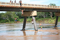 Local kids jump off the bridge to cool off at Fitzroy Crossing in the wet season.