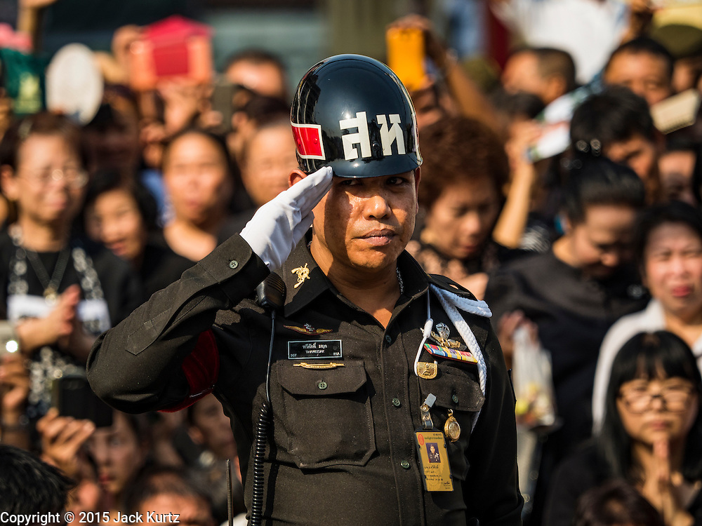 16 DECEMBER 2015 - BANGKOK, THAILAND: A Thai military policeman salutes during the funeral procession for Somdet Phra Nyanasamvara, who headed Thailand's order of Buddhist monks for more than two decades and was known as the Supreme Patriarch. He was ordained as a Buddhist monk in 1933 and appointed as the Supreme Patriarch in 1989. He was the spiritual advisor to Bhumibol Adulyadej, the King of Thailand when the King served as a monk in 1956. Tens of thousands of people lined the streets during the procession to pray for the Patriarch.     PHOTO BY JACK KURTZ