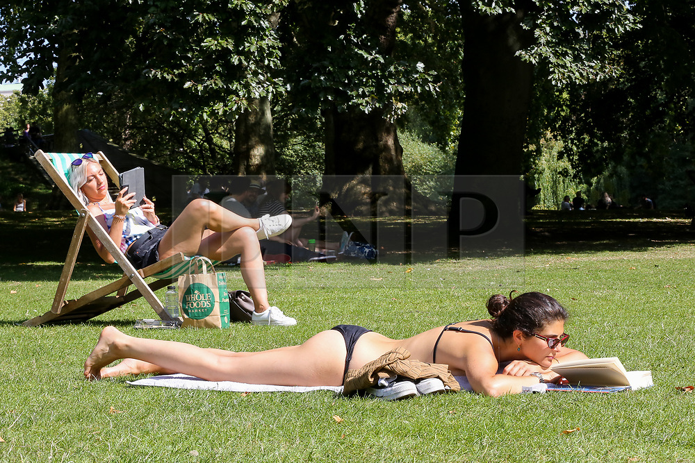 © Licensed to London News Pictures. 24/08/2019. London, UK. A woman sunbathing in London's St James's Park  while reading a book as the hot weather continues. According to the Met Office, the temperatures are forecast to reach between 31 and 33 degrees celsius in the south-east of England. <br /> <br /> ***Permission Granted***<br /> <br /> Photo credit: Dinendra Haria/LNP