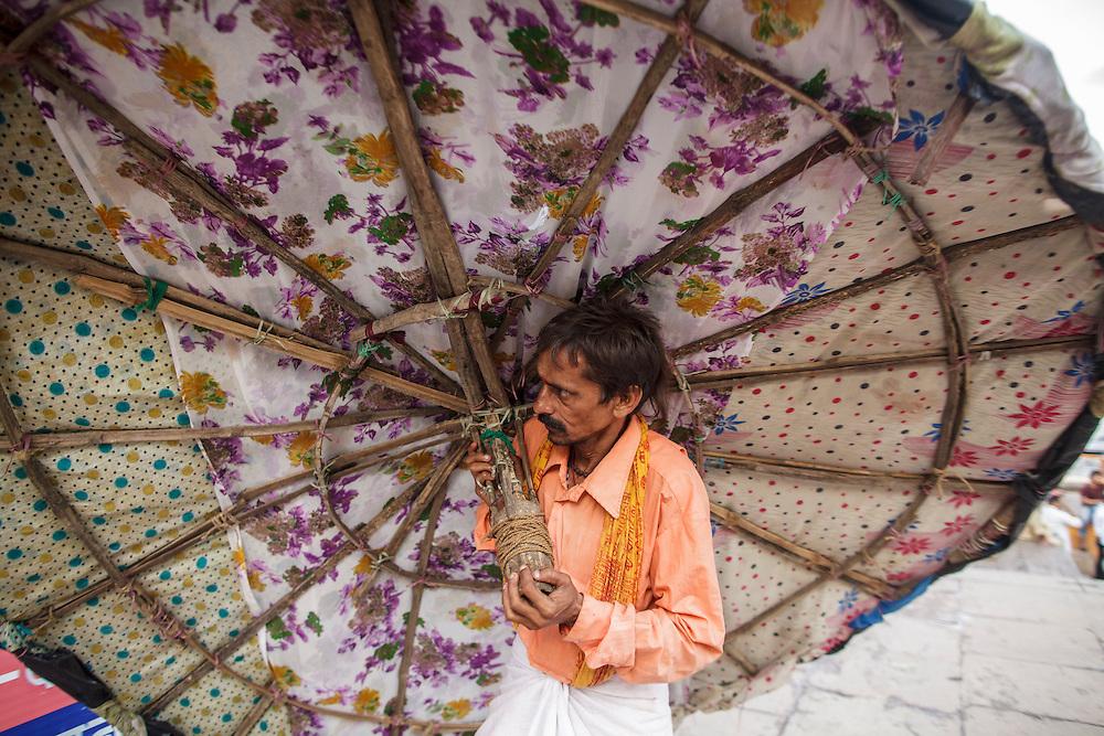A man carrying a sunshad at Dashashwamedh Gath near Ganges River in Varanasi, India.