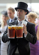 © Licensed to London News Pictures. 21/06/2012. Ascot, UK A racegoer carries jugs of Pimms. Ladies Day at Royal Ascot 21st June 2012. Royal Ascot has established itself as a national institution and the centrepiece of the British social calendar as well as being a stage for the best racehorses in the world.. Photo credit : Stephen Simpson/LNP