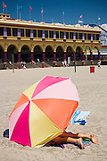 A young woman relaxes below a large colorful umbrella on the sand along the Beach Boardwalk in Santa Cruz, California.