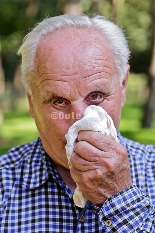 portrait of elderly man blowing his nose