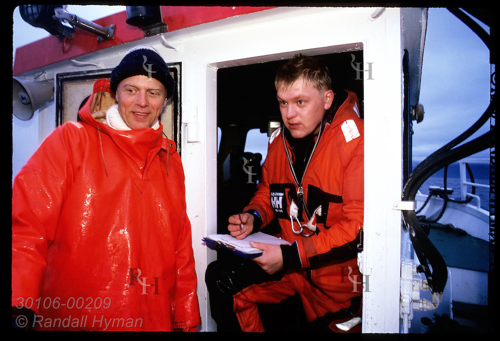Coast guard officer talks to fisherman about document problem on his gillnet boat; West Fjords Iceland