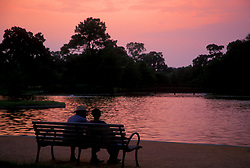 Stock photo of a man and woman sitting on a bench in at sunset in Hermann Park in near downtown Houston Texas