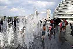Children having fun in the water spouts by City Hall, London UK July 2016