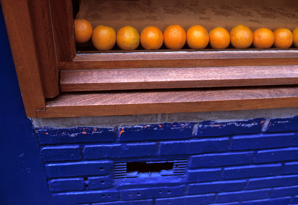A display of oranges contrasts with painted blue bricks on a store window in Paris, France.