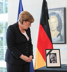June 18, 2017 - Berlin, Germany - German Chancellor ANGELA MERKEL looks at a photo of former German Chancellor Helmut Kohl (bottom) after signing the condolences book at German Chancellery. Kohl died at his home in Ludwigshafen on Friday at the age of 87. (Credit Image: © Shan Yuqi/Xinhua via ZUMA Wire)