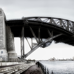 A Black and White Panoramic Photo Stith of Sydney Harbour Bridge taken from the North Shore. You can see the Opera House in the distance,