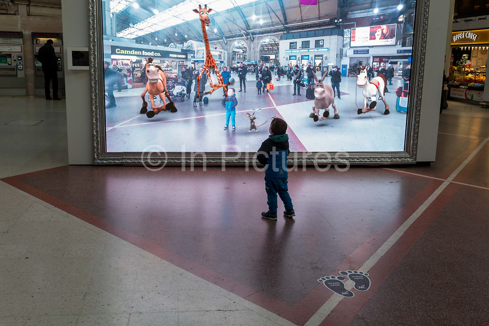 As young child is captivated by a large screen showing an augmented reality world of the station concourse and fantasy creatures, part of a loop of ads for Visit Scotland and for HBOs Game of Thrones, in London, England, on 4th December 2019.