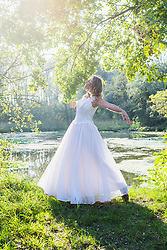View of a beautiful bride dancing by lake, Germany