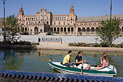 Tourists boat around Seville's Plaza de Espana, the location for 3 hundred years of Spanish Inquisition burnings. The rental boat makes its leisurely way around the waters of this medieval square. This semicircular enclosure was built by Aníbal González, the great architect of Sevillian regionalism, for the Ibero-American exposition held in 1929. Today the Plaza de España mainly consists of Government buildings. The Seville Town Hall, with sensitive adaptive redesign, is located within it. The Plaza's tiled 'Alcoves of the Provinces' are backdrops for visitors portrait photographs, taken in their own home province's alcove.
