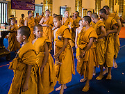 """03 APRIL 2016 - CHIANG MAI, THAILAND: Novices, young Buddhist monks, leave the """"viharn"""" or prayer hall after a meditation and prayer ceremony at Wat Chedi Luang in Chiang Mai. The meditation ceremony was in honor of the birthday of Her Royal Highness Princess Maha Chakri Sirindhorn, the daughter of Bhumibol Adulyadej, the King of Thailand. The Princess was born on April 2, 1955. She is revered by Thais and special ceremonies in her honor are held in temples throughout Thailand.     PHOTO BY JACK KURTZ"""