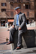 An elderly man passes the time while sitting in Piazza del Campo, Siena, Tuscany, Italy. For editorial use only.