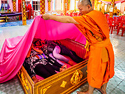 """29 MARCH 2017 - BANG KRUAI, NONTHABURI, THAILAND: A Buddhist monk pulls a pink sheet over a family in a coffin, symbolizing their death during a """"Resurrection Ceremony"""" at Wat Ta Kien (also spelled Wat Tahkian), a Buddhist temple in the suburbs of Bangkok. People go to the temple to participate in a """"Resurrection Ceremony."""" Groups of people meet and pray with the temple's Buddhist monks. Then they lie in coffins, the monks pull a pink sheet over them, symbolizing their ritualistic death. The sheet is then pulled back, and people sit up in the coffin, symbolizing their ritualist rebirth. The ceremony is supposed to expunge bad karma and bad luck from a person's life and also get people used to the idea of the inevitability of death. Most times, one person lays in one coffin, but there is family sized coffin that can accommodate up to six people. The temple has been doing the resurrection ceremonies for about nine years.          PHOTO BY JACK KURTZ"""
