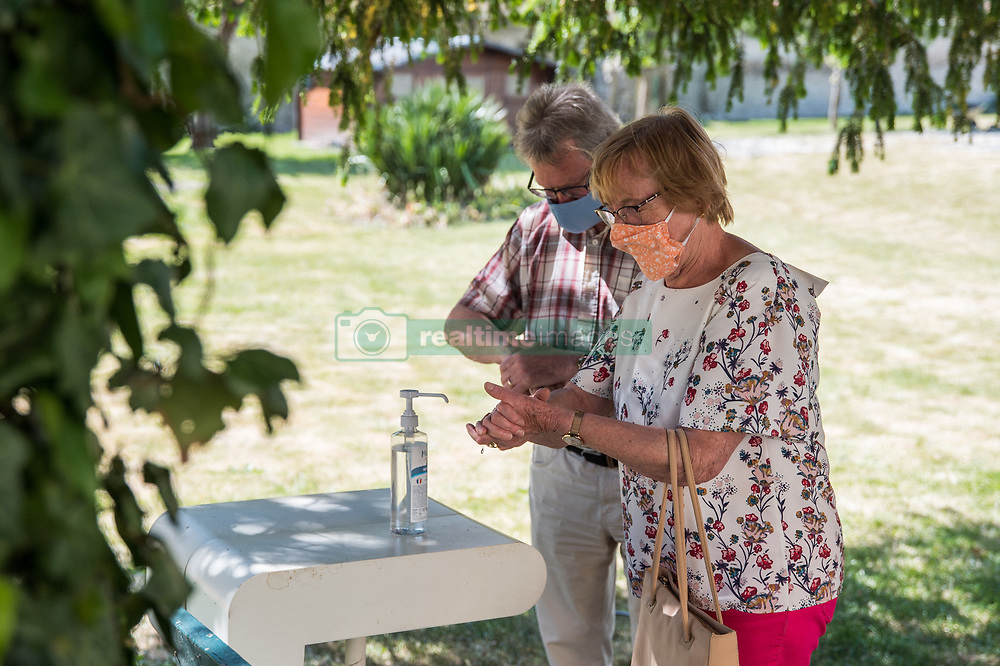 A couple washes their hands with hydroalcoolic gel after visting her cousin in a bubble at Fondation Shadet Vercoustre nursing home on May 27, 2020 in Bourbourg near Gravelines, France, where a double entry bubble has been installed to allow visits without risk of contamination, as part of a prophylactic measure against the spread of the Covid-19 disease caused by the novel coronavirus. Relatives and residents each enter the tent through a different entrance to find themselves in the same room, separated by a transparent plastic canvas. These bubbles were originally designed for tourism by the company. Photo by Julie Sebadelha/ABACAPRESS.COM