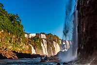Speedboat approaching a waterfall, Iguazu Falls (Iguacu in Portugese), on the border of Brazil and Argentina. It is one of the New 7 Wonders of Nature and is a UNESCO World Heritage Site. There are 275 waterfalls total which make up the largest waterfalls in the world.
