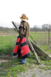 An aging man dressed in western fashions looks the part of a cowboy from days gone by in the American Old West. Accessories include a cowboy hat, boots, denim, sisal rope, western style belt, western duster and a saddle blanket. Wood and Steel fence posts are stacked together with the spares leaning against strands of barbed wire that complete the fence. This image available for EDITORIAL USE ONLY. A release may be required. Additional information by contacting alook at alanlook.com