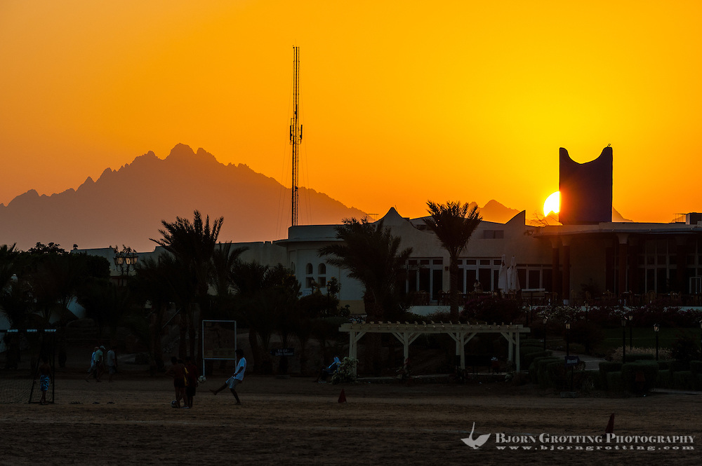 Egypt, Hurghada. Children playing football in the sunset.