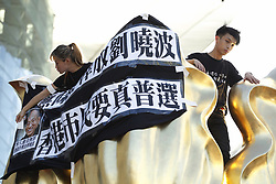 June 28, 2017 - Hong Kong, CHINA - Two pan democrat protesters climb up on top of Statue Of Golden Bauhinia, a symbol of HKSAR displaying a black cloth that carry a slogan which reads Unconditional Release Of Liu Xiao Bo, Hong Kong Citizens Demand Universal Suffrage after they have staged a political demonstration protesting Chinese President Xi Jin Pings visit.(Credit Image: © Liau Chung Ren via ZUMA Wire)