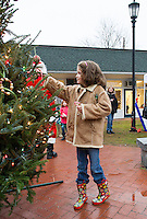 Abigail Seal helps to decorate a Christmas tree in Meredith Park on Saturday afternoon with homemade ornaments in conjunction with the Greater Meredith Program.  (Karen Bobotas/for the Laconia Daily Sun)